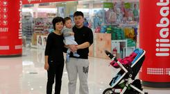 Zhao Xingqiu (27) with her husband and their baby in Beijing. An office worker, she does not plan to have a second child. When she heard about the rule change of one-child policy, she thought it could not change much because there are some difficulties in raising children in China. Photo: Reuters
