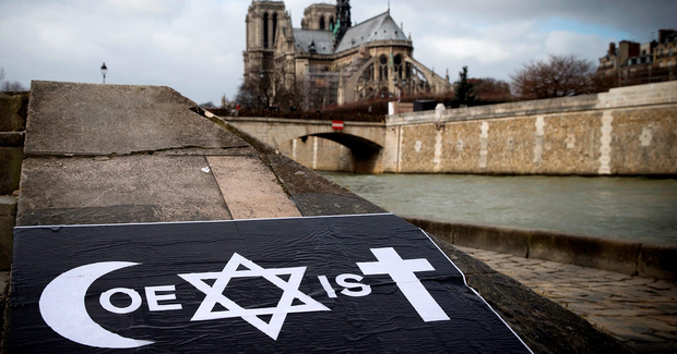 A poster by French street artist Combo is pictured after being stuck on the Quai de la Tournelle, near the Arab World Institute (IMA) on February 8, 2015 in Paris, displaying Combo's message on the coexistence of religions, using intertwined symbols of the Muslim, Jewish and Catholic religions to write the word