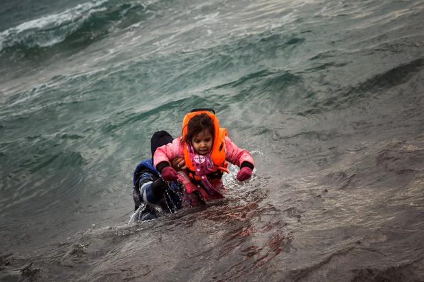 A man carries a child as they try to reach a shore after falling into the sea while disembarking from a dinghy on which they crossed a part of the Aegean sea with other refugees and migrants, from Turkey to the Greek island of Lesbos. Photo: AP Photo/Santi Palacios