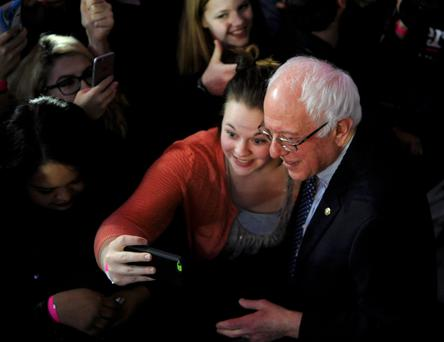 Bernie Sanders poses for a selfie with a supporter during his caucus night rally in Des Moines, Iowa