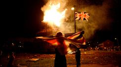 A boy holds a Union flag in front of a bonfire burning in the Shankill Road area of Belfast ahead of the Twelfth of July celebrations. The Twelfth is based on fantasies about past glories – but the new Irish GDP figures are equally fantastical. Photo: Reuters