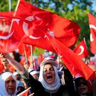 Supporters wave flags as they wait for Turkish President Tayyip Erdogan to appear for a speech outside his home in Istanbul. Photo: Reuters
