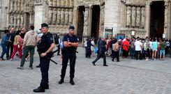 Policemen stand guard in front of Notre Dame Cathedral in Paris as people wait in line to pay tribute to murdered priest Fr Jacques Hamel. Photo: Getty