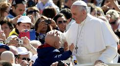 Pope Francis blesses a child as he arrives to lead the weekly audience in Saint Peter's Square. Photo: Getty