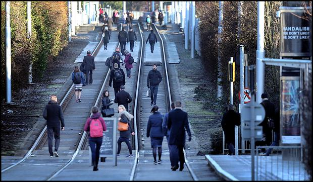 Commuters walk to town along the Luas tracks at Ranelagh during the Luas strikes in February. Photo: Steve Humphreys