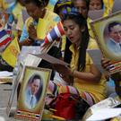 Well-wishers pray next to a portrait of Thailand's King Bhumibol Adulyadej at Siriraj hospital, where a group has gathered in Bangkok. REUTERS