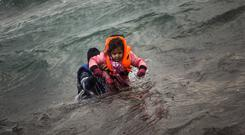 A man carries a child as they try to reach a shore after falling into the sea while disembarking from a dinghy on which they crossed a part of the Aegean sea, from Turkey to the Greek island of Lesbos earlier this year.