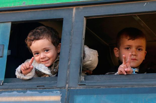 A Syrian boy evacuated from rebel-held neighbourhoods in the embattled city of Aleppo, gestures as he is evacuated.