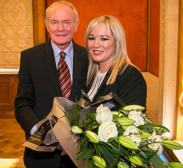 Martin McGuinness presents Michelle O'Neill, his successor as Sinn Féin leader in the North, with some flowers on her appointment in January. Photo: PA
