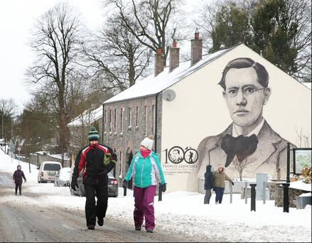 Beast from the east hits meath: Local people do their best to keep warm as they pass the portrait of World War I poet Francis Ledwidge in his home town of Slane. Photo: David Conachy