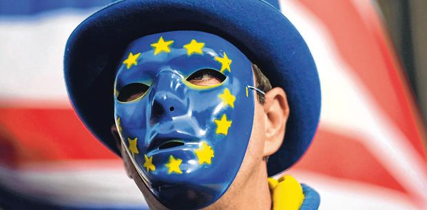 Facing up: An anti-Brexit demonstrator wears a mask bearing the stars of the European flag, during a protest outside the houses of Parliament, in London. Photo: AP