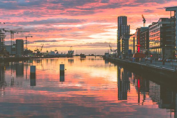 Glow of home: A majestic sunrise over Dublin Docklands and the River Liffey. For many, Ireland's attractions aren't enough to stop them leaving.
