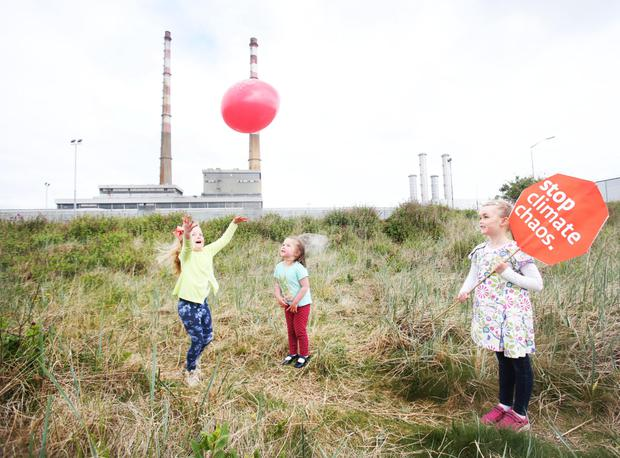 In the air: Laoise O Morain, from Sandymount, holds a Stop Climate Change sign as her sisters Aisling and Róisín play beside Poolbeg Towers in Dublin. Photo: Leon Farrell