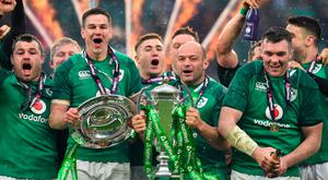 United: Rory Best holds the Six Nations trophy while Jonathan Sexton hoists Ireland's Triple Crown as players from both sides of the border celebrate their Six Nations Grand Slam victory after defeating England at Twickenham