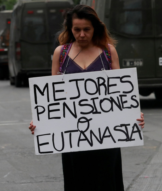 Turbulent world: A woman holds a placard reading, 'Better pensions or euthanasia' during a protest against Chile's government in Santiago this week. Photo: Reuters