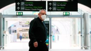 Following the rules: A priest wearing a protective face mask at Terminal 2 in Dublin Airport during the Covid-19 lockdown. PHOTO: BRIAN LAWLESS/PA