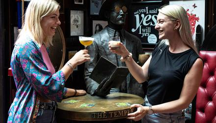 Yvonne Meppelink (left) and Sacha Wassenaar, visiting from the Netherlands, enjoy a drink in the Temple Bar in Dublin as pubs and restaurants reopened after Covid restrictions were eased. Photo: Damien Eagers/PA