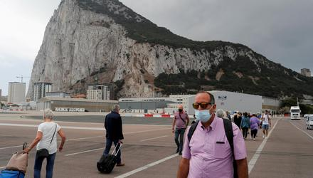 People cross the tarmac of the airport in front of the Rock of Gibraltar in the British overseas territory of Gibraltar. Photo: Reuters/Jon Nazca