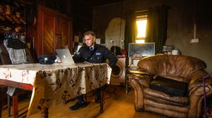 Respect: Sgt Fergus Gaughan watches the online funeral of Nora NÍ Mháille in Carraroe, Co Galway.Photo: Mark Condren