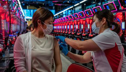 A woman receives the Moderna coronavirus vaccine in a pachinko parlour in Osaka, Japan. Photo: Carl Court/Getty Images