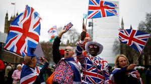 Flying the flag: People celebrate at Parliament Square in London. Photo: Henry Nicholls/Reuters
