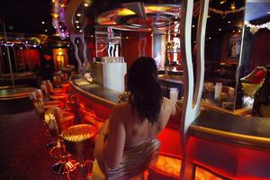 Red light: A prostitute poses at the bar of Berlin's Artemis brothel. Photo: Getty Images