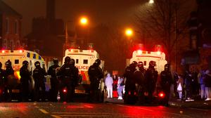 Police officers stand near their vehicles during a riot at Lanark Way in Belfast. Photo: Reuters/Jason Cairnduff