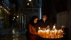 A couple lights candles during Palm Sunday mass in the Church of the Holy Sepulchre in the Old City of Jerusalem, Sunday, March 28 2021. After a year of coronavirus restrictions, Holy Week celebrations are resuming. Photo: Maya Alleruzzo/ AP Photo