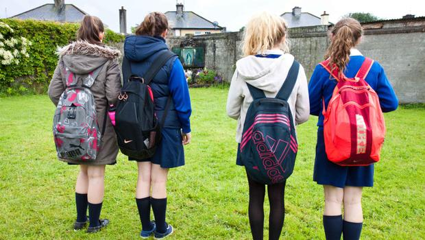 Schoolgirls pay their respects at the site of the unmarked grave at the mother and babies home in Tuam, Co Galway. Photo: Andy Newman