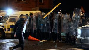Objects are thrown towards PSNI officers with riot shields in Belfast during further unrest. Photo: Liam McBurney/PA Wire