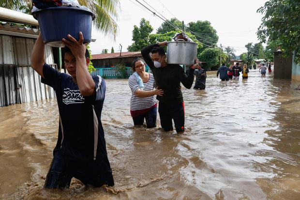 Residents wade through floodwaters carrying their belongings after flooding in Suyapa, Honduras