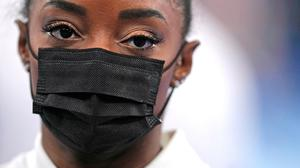US gymnast Simone Biles stands wearing a mask after she exited the team final with apparent injury, at the 2020 Summer Olympics on Tuesday in Tokyo. The 24-year-old reigning Olympic gymnastics champion Biles huddled with a trainer. Photo: Gregory Bull/AP