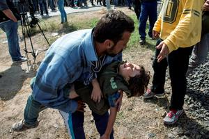 A refugee seeks help for an ill child in Hungary yesterday