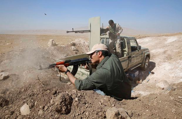 A Kurdish Peshmerga fighter fires at Baretle village, which is controlled by the Islamic State, in Khazir, on the edge of Mosul