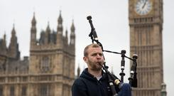 Bagpiper Craig Lawrie plays on Westminster Bridge in front of the Houses of Parliament on September 17, 2014 in London, England