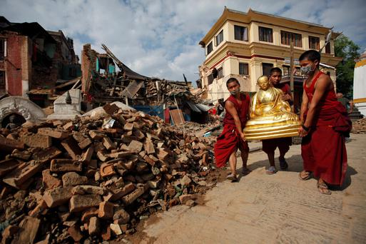 Buddhist monks salvage a statue of a Buddhist deity from a monastery around the famous Swayambhunath stupa after it was damaged by Saturday's earthquake in Kathmandu, Nepal.