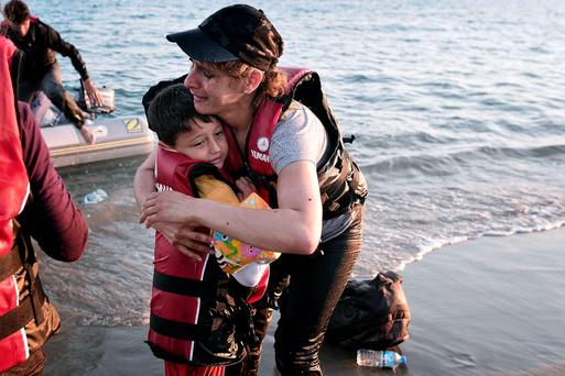 A migrant hugs her son after safely arriving on a beach on the Greek island of Kos