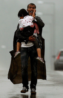 A refugee father carries his child on the border in Macedonia