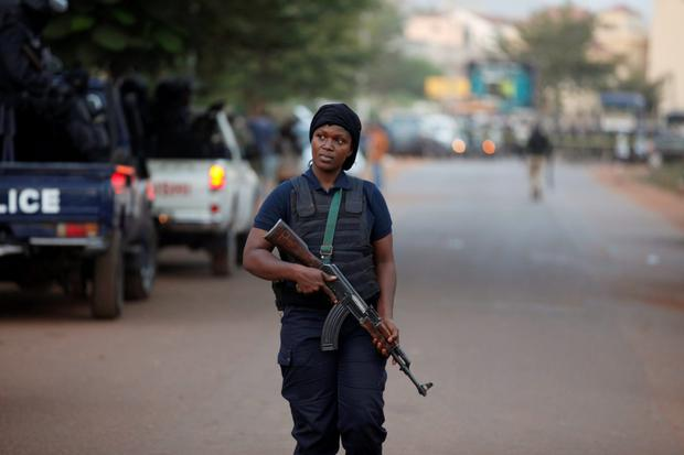 A Malian police officer walks in front of the Radisson hotel in Bamako, Mali