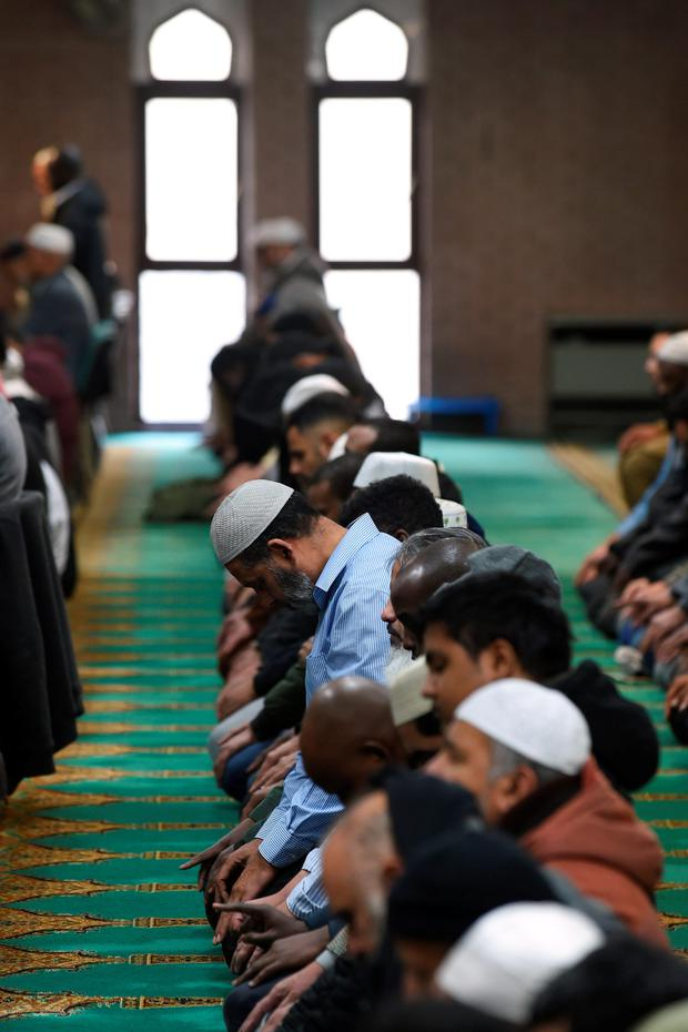 Muslim men observe a minute's silence after their prayers inside Birmingham Central Mosque to remember the victims of last Friday's attacks in Paris