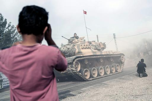 A boy looks on as Turkish tanks move toward the Syrian border, in Karkamis, Turkey on Thursday. Photo: AP/Halit Onur Sandal