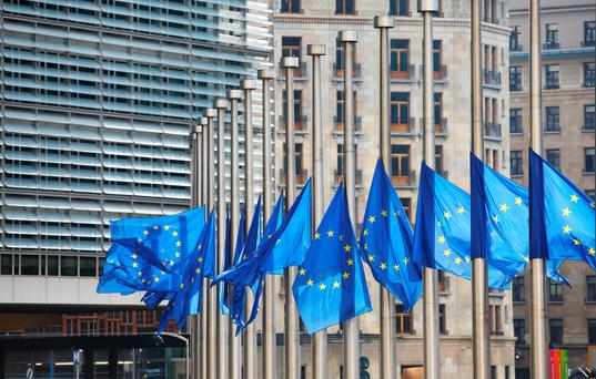 European Union flags fly at half-mast outside the European Council building in Brussels. Photo: Bloomberg
