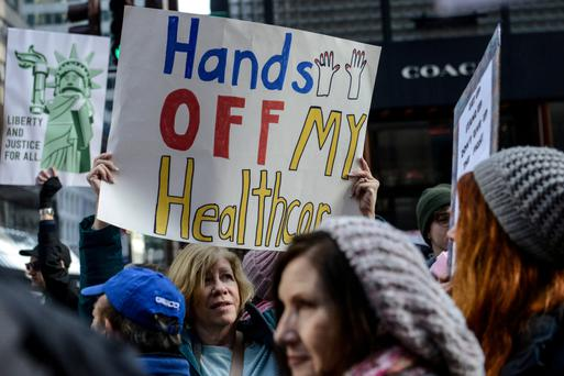 A woman holds a sign reading 'Hands off my healthcare' during protests. Photo: Reuters/Stephanie Keith