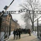 Visitors walk under the gate of the former Auschwitz Nazi concentration camp in Poland. Photo: Kacper Pempel/Reuters