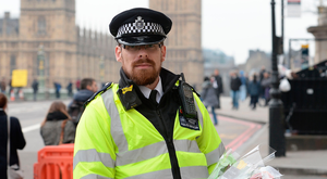 A police officer holding flowers on Westminster Bridge in London