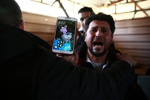 A Syrian shows a picture of his daughter, who died in an airstrike on the rebel-held besieged city of Douma. Photo: Bassam Khabieh/Reuters