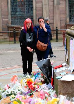 An Ariana Grande fan and her mother lay flowers in St Ann's Square, close to the Manchester Arena. Photo: PA