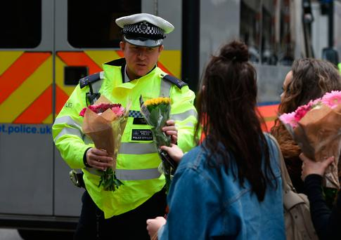 A woman asks a police officer to lay flowers near London Bridge. Photo: PA
