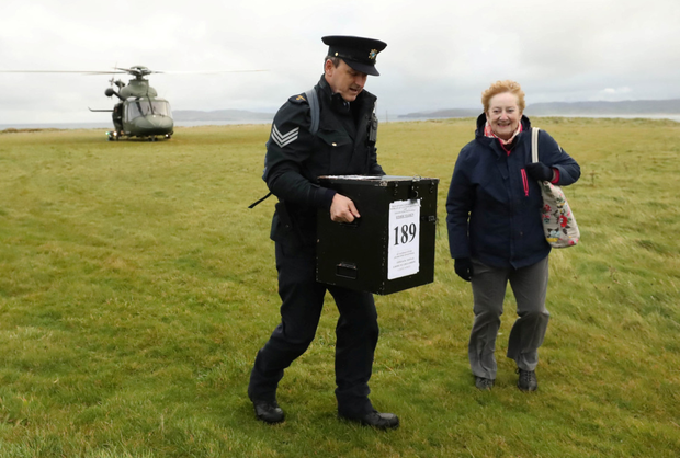 Decision time: Garda Sgt John Gallagher and presiding officer Carmel McBride arrive by helicopter yesterday with a ballot box for the vote on Inishbofin island, Co Donegal. Photo: Reuters