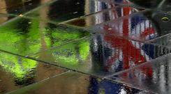 Police officers are reflected in a wet pavement as they walk past flags tied to railings by anti-Brexit demonstrators. Stock picture